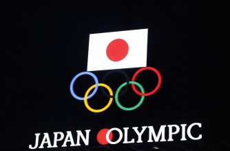 Olympic Rings and a Japan flag are seen on the Japan Olympic Museum building in Tokyo on January 8, 2021, as Tokyo Olympics organisers insisted that the coronavirus-postponed Games will still go ahead despite Japan declaring a state of emergency less than 200 days before the opening ceremony. (Photo by Behrouz MEHRI / AFP)