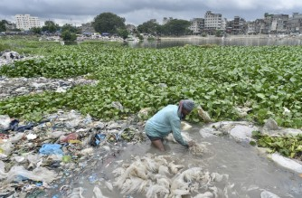 A man cleans plastic bags to be recycled at Buriganga river during a lockdown imposed by the Bangladesh's government to curb the spread of the Covid-19 coronavirus in Dhaka on July 28, 2021. (Photo by Munir Uz zaman / AFP)
