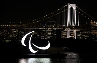 The Paralympics symbol is seen lit up at night with the Rainbow bridge in the background, on the Odaiba waterfront in Tokyo on August 23, 2021. (Photo by Charly TRIBALLEAU / AFP)