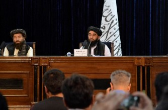 Taliban spokesperson Zabihullah Mujahid (R) listens to a question during a press conference in Kabul on August 24, 2021 after the Taliban stunning takeover of Afghanistan. (Photo by Hoshang Hashimi / AFP)