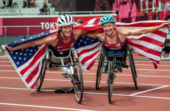 Bronze medalist USA's Tatyana McFadden (L) and Gold medalist USA's Susannah Scaroni celebrate after the women's 5000m - T53/54 of the Tokyo 2020 Paralympic Games at the Olympic Stadium in Tokyo on August 28, 2021. (Photo by Philip FONG / AFP)