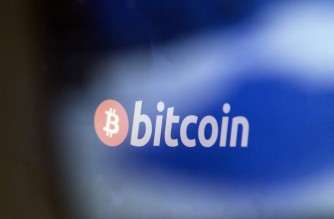 This picture taken at La Maison du Bitcoin in Paris on January  17, 2018 shows a bitcoin logo. (Photo by GEOFFROY VAN DER HASSELT / AFP)