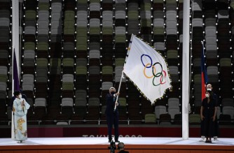 President of the International Olympic Committee (IOC) Thomas Bach waves the Olympic flag between Tokyo's governor Yuriko Koike (L) and Paris Mayor Anne Hidalgo (R), during the closing ceremony of the Tokyo 2020 Olympic Games, on August 8, 2021 at the Olympic Stadium in Tokyo. (Photo by Jewel SAMAD / AFP)