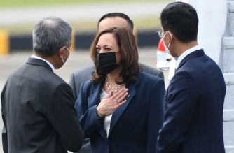 US Vice President Kamala Harris (C) is greeted by Singapore's Foreign Minister Vivian Balakrishnan (L) upon her arrival at Paya Lebar Base airport in Singapore on August 22, 2021. (Photo by Roslan Rahman / AFP)
