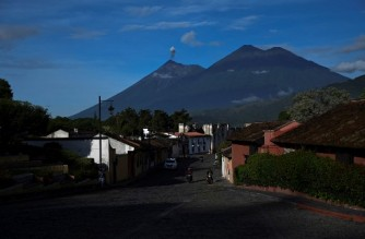 The Fuego Volcano (L) spews ash as seen from Antigua Guatemala, Sacatepequez Departament, 45 km southeast of Guatemala City on September 6, 2020. - Since the economic reopening a month ago, the colonial city of Antigua, a Cultural Heritage of Humanity, is receiving local visitors under strict hygiene measures to avoid coronavirus contagion. But the city is waiting for the reopening of the international airport and borders to see the arrival of foreign tourists, its main income. (Photo by Johan ORDONEZ / AFP)