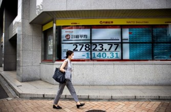 A pedestrian walks past a stock indicator displaying numbers of the Nikkei 225 of the Tokyo Stock Exchange in Tokyo on June 21, 2021. (Photo by Behrouz MEHRI / AFP)