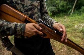 """This photo taken on July 7, 2021 shows a member of the Karenni People Defense Force (KPDF) holding a homemade gun adorned with the words """"Spring Revolution"""" in Myanmar script as he takes part in training at a camp near Demoso in Kayah state. - In their camp hidden in the forested hills of Kayah state near the Thai border, Myanmar anti-junta volunteers practice firing their homemade weapons, do physical training, and play guitar in between skirmishes with the military. (Photo by STR / AFP) / To go with 'MYANMAR-POLITICS-MILITARY-COUP,PHOTOESSAY'"""