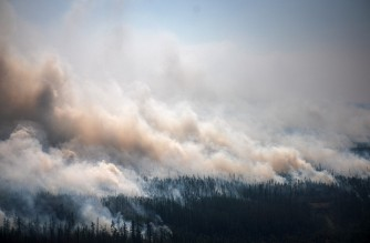 This aerial picture taken from an airplane on July 27, 2021, shows the smoke rising from a forest fire outside the village of Berdigestyakh, in the republic of Sakha, Siberia. - Russia is plagued by widespread forest fires, with the Sakha-Yakutia region in Siberia being the worst affected. According to many scientists, Russia -- especially its Siberian and Arctic regions -- is among the countries most exposed to climate change. The country has set numerous records in recent years and in June 2020 registered 38 degrees Celsius (100.4 degrees Fahrenheit) in the town of Verkhoyansk -- the highest temperature recorded above the Arctic circle since measurements began. (Photo by Dimitar DILKOFF / AFP)