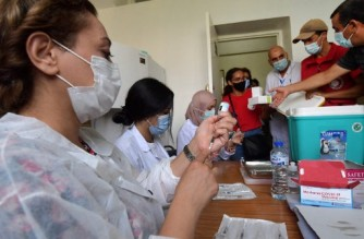 Tunisian medics prepare doses of the covid Moderna vaccine at an inoculation center in the capital Tunis, on August 15, 2021. - Tunisian Health Director General Faycel Ben Salah said nearly 1 million people will be called to the 2nd day of intensive coronavirus vaccination to be held on August 15, targeting the 18-39 age group. (Photo by FETHI BELAID / AFP)