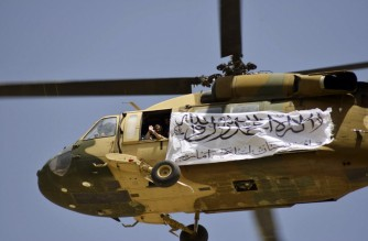 A helicopter displaying a Taliban flag flies above Taliban supporters gathered to celebrate the US withdrawal of all its troops out of Afghanistan, in Kandahar on September 1, 2021 following the Taliban's military takeover of the country. (Photo by JAVED TANVEER / AFP)