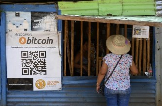 A woman buys in a store that accepts bitcoins in El Zonte, La Libertad, El Salvador on September 4, 2021. - The Congress of El Salvador approved in June a law that will make bitcoin legal tender in the country from September 7, with the aim of boosting its economy although analysts warn of a negative impact. (Photo by MARVIN RECINOS / AFP)
