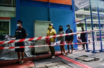 This photo taken on September 6, 2021 shows Khlong Toei residents queuing for rapid antigen tests, which screen for the Covid-19 coronavirus, administered by volunteers from the Bangkok Community Help Foundation in Bangkok. (Photo by Lillian SUWANRUMPHA / AFP)