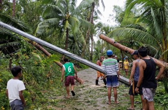 This photo taken on September 7, 2021 shows residents and electric company personnel trying to repair a fallen electric post next to an uprooted coconut tree at a village in Hernani town, Eastern Samar province, central Philippines, a day after Tropical Storm Conson made its first landfall in the town. (Photo by Blissy Vista / AFP)