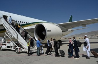 Passengers board a Pakistan International Airlines (PIA) flight, the first commercial international flight since the Taliban retook power last month, at the airport in Kabul on September 13, 2021. (Photo by Aamir QURESHI / AFP)