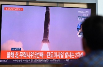 A man watches a television news broadcast showing file footage of a North Korean missile test, at a railway station in Seoul on September 15, 2021, after North Korea fired two ballistic missiles into the sea according to the South's military. (Photo by Jung Yeon-je / AFP)