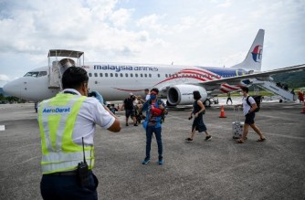 A ground staff member (L) helps to take pictures of a passenger after he disembarked from a Malaysia Airlines Boeing 738 aircraft upon its landing in Langkawi from Kuala Lumpur International Airport on September 16, 2021, as the holiday island reopened to domestic tourists following closures due to restrictions to halt the spread of the Covid-19 coronavirus. (Photo by Mohd RASFAN / AFP)