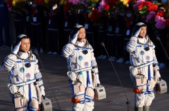 (FILES) This file photo taken on June 17, 2021 shows astronauts Nie Haisheng (C), Liu Boming (R) and Tang Hongbo saluting during a departure ceremony before boarding the Shenzhou-12 spacecraft on a Long March-2F carrier rocket at the Jiuquan Satellite Launch Centre in the Gobi desert in northwest China. - Chinese astronauts returned to earth on September 17, 2021 after completing the country's longest-ever crewed mission, the latest landmark in Beijing's drive to become a major space power. (Photo by GREG BAKER / AFP)