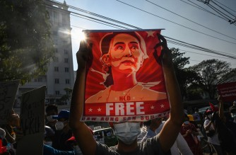 (FILES) In this file photo taken on February 15, 2021, a protester holds up a poster featuring Aung San Suu Kyi during a demonstration against the military coup at in front of the Central Bank of Myanmar in Yangon. - Myanmar's junta will put ousted leader Aung San Suu Kyi on trial for corruption, her lawyer said on September 17, 2021, adding to a raft of ongoing cases that could see her jailed for decades. (Photo by STR / AFP)
