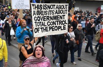 Protesters march through the streets during an anti-lockdown rally in Melbourne on September 18, 2021. (Photo by William WEST / AFP)
