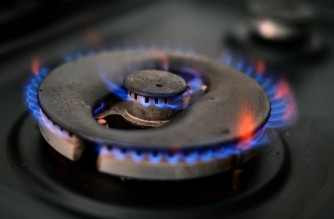 A photo illustration shows gas burning on a domestic hob in Liverpool, north-west England on September 20, 2021. - The UK government was on Monday holding an emergency meeting with energy and consumer groups, as the country experiences record gas prices that threaten huge bills for households as well as undermining food supplies and casting doubt on energy firms' futures. (Photo by Paul ELLIS / AFP)