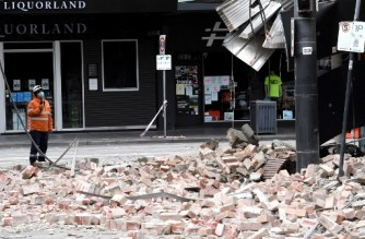 An emergency and rescue official examine the damage to a building in the popular shopping Chapel Street in Melbourne on September 22, 2021, after a 5.9 magnitude earthquake. (Photo by William WEST / AFP)
