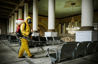 A serviceman of Russia's Emergencies Ministry, wearing protective gear, disinfects Kievsky railway terminal amid the COVID-19 pandemic in Moscow on September 2021. (Photo by Alexander NEMENOV / AFP)