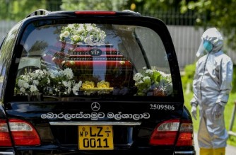 A cemetery worker wearing Personal Protective Equipment (PPE) stand next to a hearse carrying the coffin of Eliyantha White, a local shaman who claimed he had super natural powers to end the pandemic and died of the Covid-19 coronavirus, at the crematorium of the Colombo General Cemetery  on September 23, 2021. (Photo by ISHARA S. KODIKARA / AFP)