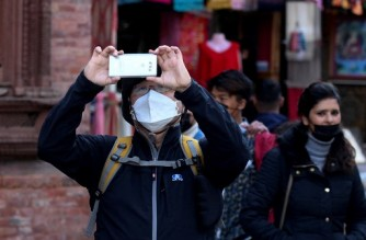 (FILES) In this file photo taken on January 30, 2020 a foreign tourists wearing a protective facemask takes pictures while visiting Basantapur Durbar Square in Kathmandu. - Nepal has restarted visas on arrival for vaccinated tourists leading attempts by South Asian nations to revive tourism businesses from 18 months of pandemic devastation. (Photo by PRAKASH MATHEMA / AFP)