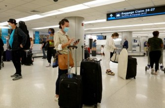 MIAMI, FLORIDA - SEPTEMBER 20: Travelers gather their luggage as they arrive at Miami International Airport on September 20, 2021 in Miami, Florida. The U.S. government announced that it will ease airline restrictions on travel into the United States for people who have vaccination proof and a negative COVID-19 test.   Joe Raedle/Getty Images/AFP (Photo by JOE RAEDLE / GETTY IMAGES NORTH AMERICA / Getty Images via AFP)