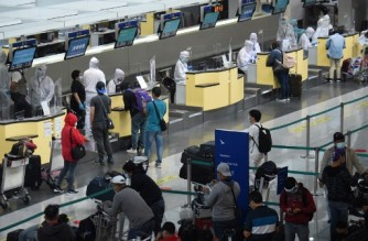 Airline ground staff (L) wearing protective gear work at the counter at the airport in Manila on August 4, 2020. - More than 27 million people -- a quarter of the Philippine population -- were give 24-hours notice of the new restrictions that have shuttered many businesses, halted public transport and grounded flights in the capital and four surrounding provinces as the government battles to rein in the virus. (Photo by Ted ALJIBE / AFP)