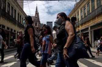 People wearing face masks walk on a pedestrian crossing in downtown Rio de Janeiro, Brazil, on December 08, 2020 amid the coronavirus (COVID-19) pandemic. (Photo by MAURO PIMENTEL / AFP)