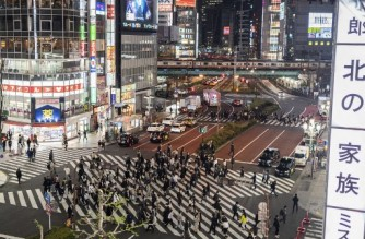 Pedestrians cross a street at night in Tokyo's Shinjuku area on April 2, 2021 as the city reported 440 new infections of the Covid-19 coronavirus. (Photo by CHARLY TRIBALLEAU / AFP)