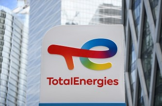This photograph taken on May 28, 2021 shows the new TotalEnergies logo during its unveling ceremony, at a charging station in La Defense on the outskirts of Paris. - Total shareholders voted on the strategy of the oil and gas giant, which renamed itself TotalEnergies to mark its diversification, while some investors are urging it to act more quickly. (Photo by Christophe ARCHAMBAULT / AFP)