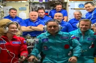 """This handout video grab taken and released on October 5, 2021 by NASA shows crew members, actress Yulia Peresild (L), cosmonaut Anton Shkaplerov (C) and film director Klim Shipenko entering the International Space station. - Russia launched an actress and a film director into space in a bid to best the United States to the first movie in orbit. (Photo by Handout / NASA / AFP) / RESTRICTED TO EDITORIAL USE - MANDATORY CREDIT """"AFP PHOTO / NASA """" - NO MARKETING - NO ADVERTISING CAMPAIGNS - DISTRIBUTED AS A SERVICE TO CLIENTS"""