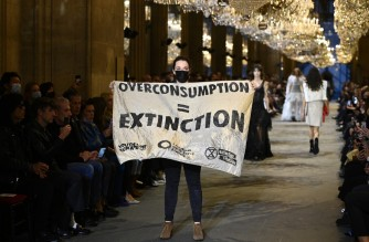 A demonstrator holds a banner as models present creations by Louis Vuitton during the Women's Spring-Summer 2022 Ready-to-Wear collection fashion show as part of Paris Fashion Week at the Louvre in Paris, on October 5, 2021. - Extinction Rebellion activists burst into the Louis Vuitton fashion show at the Louvre to denounce the impact of the fashion industry on climate change, on the last day of Paris Fashion Week. (Photo by Christophe ARCHAMBAULT / AFP)
