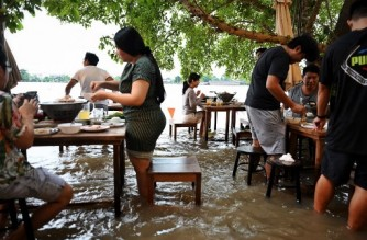 This photo taken on October 7, 2021, shows people standing up whilst enjoying dinner at the Chaopraya Antique Cafe, as flood water from the Chao Phraya River surges into the restaurant, in Nonthaburi province north of Bangkok. (Photo by Lillian SUWANRUMPHA / AFP)