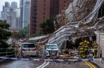 Rescue personnel at the scene where bamboo scaffolding by a high-rise residential building collapsed onto a road, following strong winds and heavy rain from weather patterns from a tropical storm, in Hong Kong on October 8, 2021. (Photo by ISAAC LAWRENCE / AFP)