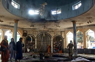 EDITORS NOTE: Graphic content / Taliban fighters investigate inside a Shiite mosque after a suicide bomb attack in Kunduz on October 8, 2021. (Photo by - / AFP)