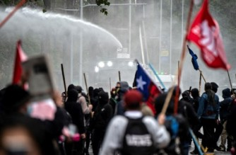 Demonstrators clash with riot police during a protest of Mapuche indigenous people in downtown Santiago, on October 10, 2021, amid the commemoration of the Day of the Race. (Photo by MARTIN BERNETTI / AFP)
