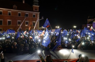 """Participants show the light of their mobile phones and wave EU flags over a large Polish flag as they take part in a pro-EU demonstration following a ruling of the Constitutional Court against the primacy of EU law in Poland, in front of the Royal Castle at the central square in Warsaw on October 10, 2021. - Tens of thousands of Poles rallied on October 10 in defence of their country's EU membership, after Poland's top court last week issued a landmark ruling against the primacy of EU law. The pro-EU demonstrations were called by former EU chief Donald Tusk, now leader of the country's main opposition grouping, Civic Platform, who has warned of the prospect of a """"Polexit"""". (Photo by Wojtek Radwanski / AFP)"""