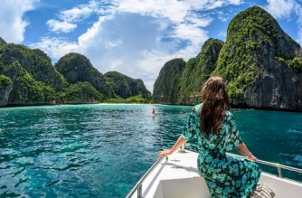 (FILES) In this file photo taken on October 4, 2019, a tourist poses for a photo on a boat before a boundary line set by the Thai National Park, Wildlife and Plant Conservation Department to close the beach on Maya Bay to visitors on the southern Thai island of Koh Phi Phi. - Thailand plans to fully re-open to vaccinated tourists travelling by air from countries deemed low risk from November 1, Premier Prayut Chan-O-Cha said on October 11, 2021. (Photo by Mladen ANTONOV / AFP)