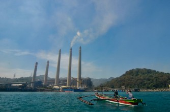 This photo taken on September 22, 2021 shows fishermen on their boat as smoke rises from chimneys at the Suralaya coal power plant in Cilegon. - Smokestacks belch noxious fumes into the air from a massive coal-fired power plant on the Indonesian coast, a stark illustration of Asia's addiction to the fossil fuel which is threatening climate targets. (Photo by RONALD SIAGIAN / AFP) / TO GO WITH Climate-UN-COP26-Asia-coal,FEATURE by Haeril Halim and Sam Reeves