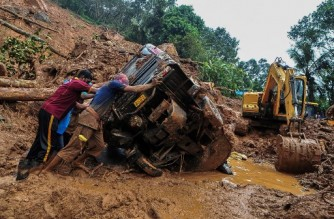 Rescue workers push a overturned vehicle stuck in the mud and debris at a site of a landslide claimed to be caused by heavy rains in Kokkayar in India's Kerala state on October 17, 2021. (Photo by - / AFP)