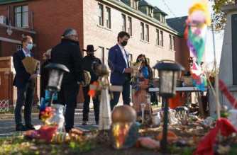 """In this photo provided by the Office of the Prime Minister of Canada, Canadian Prime Minister Justin Trudeau (R) and Minister of Indigenous Services of Canada Marc Miller (L) lay flowers at a memorial outside of the Kamloops Indian Residential School in Kamloops, British Columbia on October 18, 2021. - Canadian Prime Minister Justin Trudeau visited the indigenous community of Kamloops where the remains of 215 children were found in May at a former residential school. (Photo by Adam Scotti / Office of the Prime Minister of Canada / AFP) / RESTRICTED TO EDITORIAL USE - MANDATORY CREDIT """"AFP PHOTO /Adam SCOTTI/ Office of the Prime Minister of Canada """" - NO MARKETING - NO ADVERTISING CAMPAIGNS - DISTRIBUTED AS A SERVICE TO CLIENTS"""