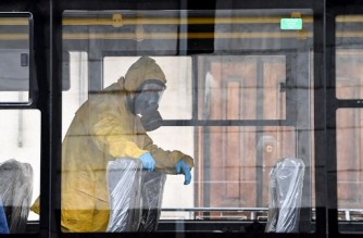 A serviceman of Russia's Emergencies Ministry wearing protective gear is seen in a bus while disinfecting Moscow's Leningradsky railway station on October 19, 2021, amid the ongoing coronavirus disease pandemic. - Russia has officially recorded 1,015 coronavirus deaths on October 19, up from 998 the previous day, and 33,740 new Covid-19 cases, down from 34,325. (Photo by Kirill KUDRYAVTSEV / AFP)