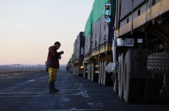 This picture taken on October 16, 2021 shows trucks loaded with coal waiting near Gants Mod port at the Chinese border with Gashuun Sukhait, in Umnugovi province, in Mongolia. - Snaking across the barren Mongolian desert, a convoy crawls along the once-busy highway to the Chinese border -- its truckers desperate to finally deliver their cargo after months of brutal Covid delays and no pay. (Photo by Uugansukh Byamba / AFP) / TO GO WITH AFP STORY  China-environment-coal-energy by Khaliun Bayartsogt