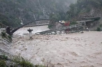 An under construction bridge is seen collapsed on a river along a national highway between Pithoragarh-Champawat, in Chalthi on October 19, 2021 following heavy rainfalls in northern India. - At least 24 people died and more than a dozen were missing after landslides and flash floods triggered by several days of heavy rain hit northern India, officials said on October 19. (Photo by AFP)