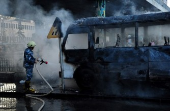 """A handout picture released by the official Syrian Arab News Agency (SANA) shows a charred Syrian army bus, that was targeted with explosive devices in the Syrian capital Damascus on October 20, 2021. - A bomb attack on an army bus in Damascus killed at least 13 people Wednesday in the bloodiest such attack in years, the SANA state news agency reported. (Photo by SANA / AFP) / == RESTRICTED TO EDITORIAL USE - MANDATORY CREDIT """"AFP PHOTO / HO / SANA"""" - NO MARKETING NO ADVERTISING CAMPAIGNS - DISTRIBUTED AS A SERVICE TO CLIENTS =="""