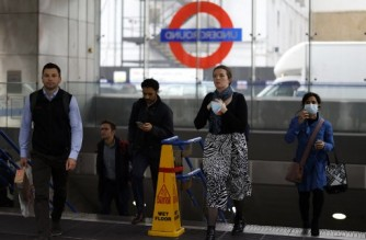 """Commuters, some wearing face coverings to help prevent the spread of coronavirus, walk out of a Transport for London (TfL) underground train station in London on October 20, 2021. - Healthcare leaders urged the British government to reinstate some coronavirus restrictions to ease pressures on hospitals because of spiralling case numbers. But ministers remain opposed to reintroducing any curbs, arguing the situation is still far better than earlier this year and the country is learning to """"live with the virus"""". (Photo by Tolga Akmen / AFP)"""