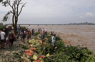People stand along the banks of flooded Karnali river following heavy rains in Rajapur village of Bardiya district in Nepal on October 20, 2021, as the death toll from days of flooding and landslides in India and Nepal crossed 100. (Photo by KRISHNA ADHIKARI / AFP)